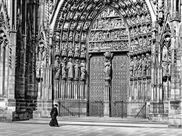 Priest walking in front of Strasbourg Cathedral, France