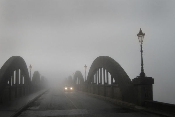 A car in thick fog on the concrete bridge over the River Dee