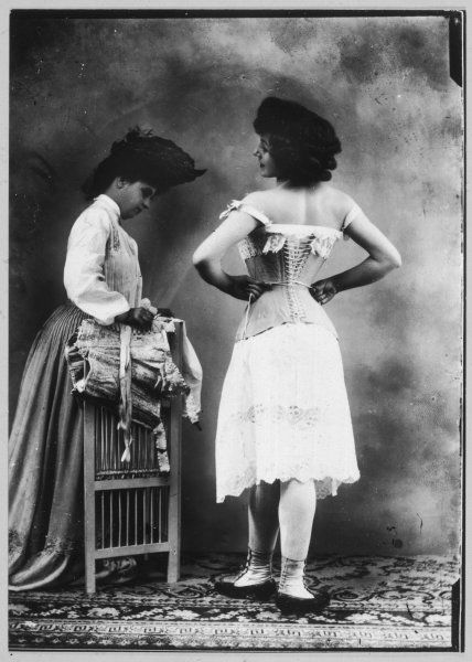 A lady tries on a corset, while another woman waits with another one