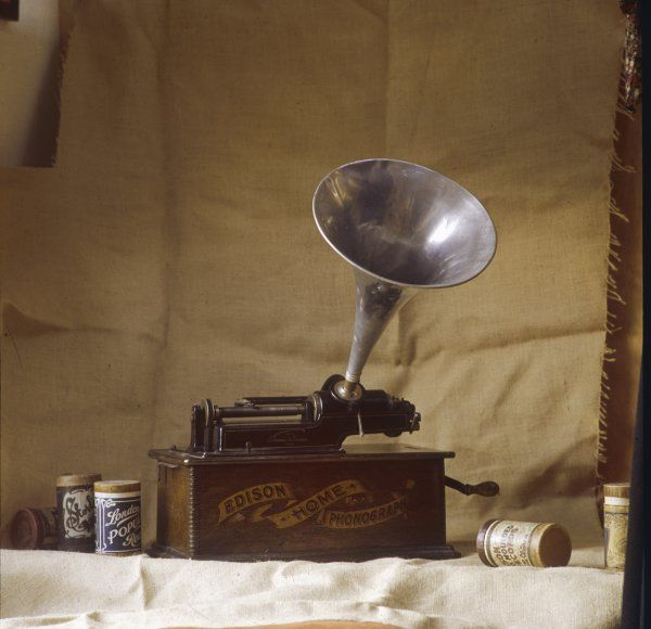An early Edison phonograph, using grooved wax cylinders, shown beside the instrument