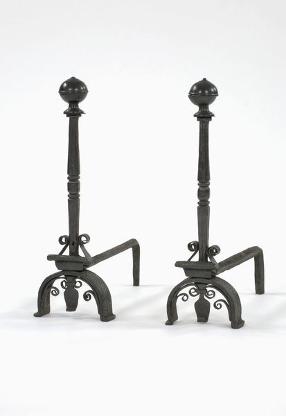 Fire dogs. One of a pair of wrought iron fire dogs with turned brass finials, arched legs