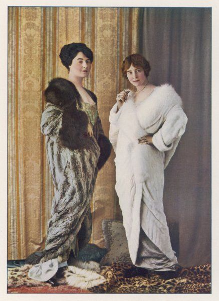 Two 'cocoon' style evening mantles in unspecified furs - one in white the other in grey with dark brown collar & cuffs. The women stand on spotted cat skin rugs
