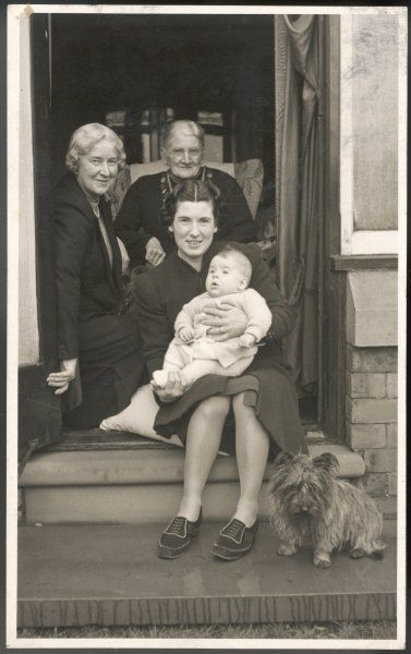 Four generations of women sitting in a doorway - and a dog