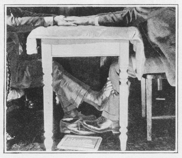 Houdini demonstrates how a foot can be released under a seance table while the fraudster is seemingly under control