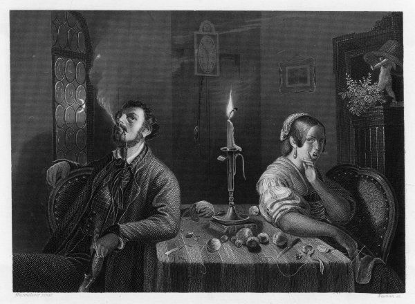 A young couple sitting at the table with their backs to one another following a tiff