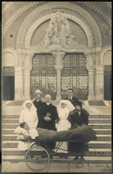 A sick pilgrim on a wheeled stretcher, with family, priest and nurses