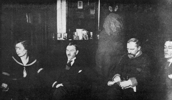 A mysterious figure, swathed in a white shroud, appears behind Kluski at a Warsaw seance