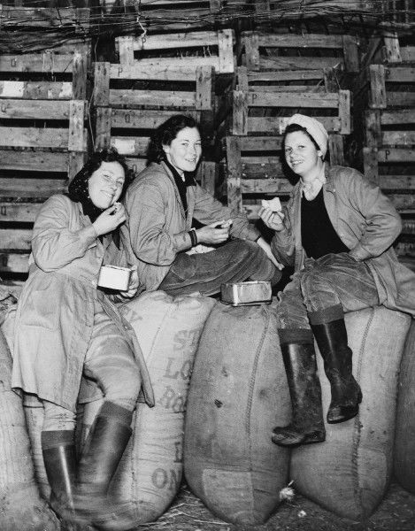 Land Girls WWII. Land Girls eating lunch in a barn during World War II