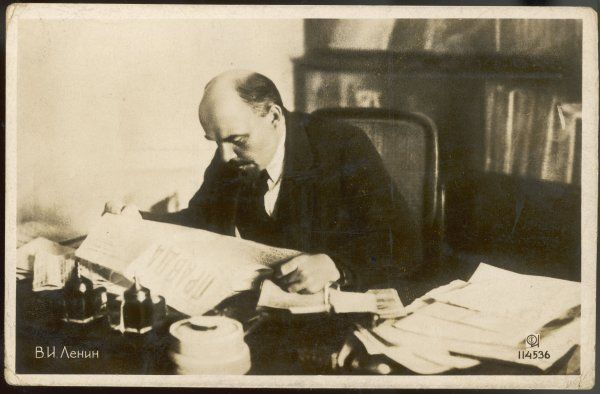 VLADIMIR ILICH ULYANOV LENIN Russian statesman, reading a copy of 'Pravda' in his study