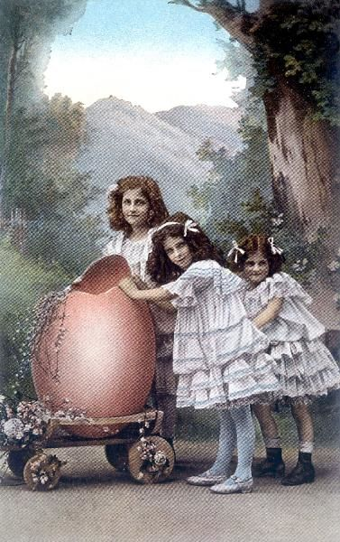 Three little girls with a large pink Easter egg, so big they have to wheel it on a trolley