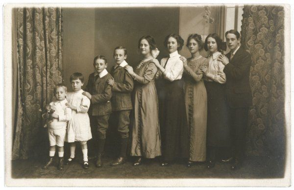 A mother and her eight children stand in a line in descending order