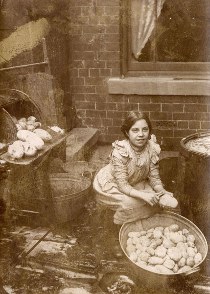 A young girl peeling a large tub Potatoes in the rear yard of a Fish & Chip Shop at Morecambe, Lancashire. Date: circa 1901