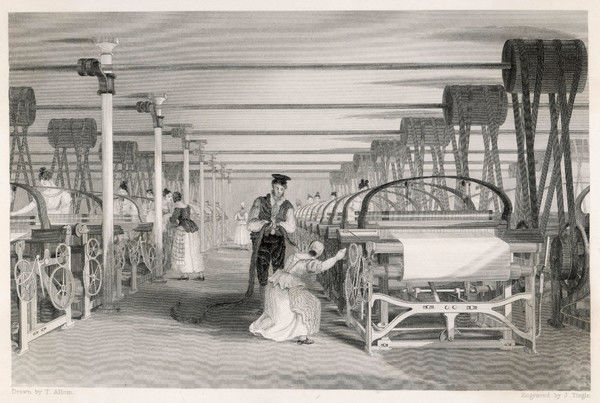 Interior of cotton mill in Lancashire: power loom weaving- man and woman tend machine