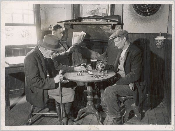 PUB DOMINOES 1930S. A game of dominoes in an English country pub