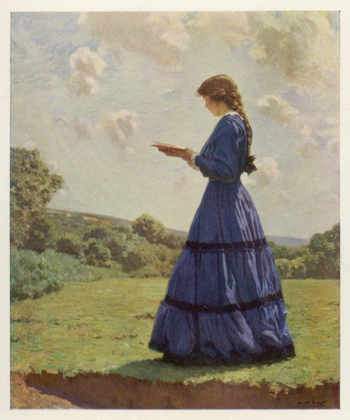 READING IN A FIELD. A girl stands in a field reading her book