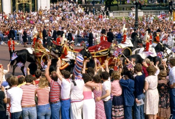 Crowds, dressed mainly in patriotic red, white and blue, line the route from Buckingham Palace to St Paul's Cathedral on the day of the Royal wedding between Prince Charles and Lady Diana Spencer, and cheer the groom and his best man, Prince