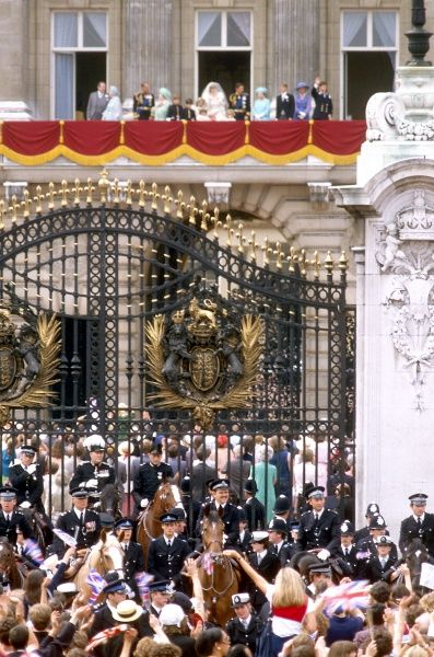Police line up by the gates of Buckingham Palace as the newly married Prince and Princess of Wles appear on the balcony of Buckingham Palace to wave to the gathered crowds of well wishers. Date: 1981