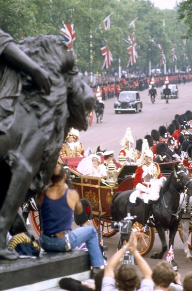 The carriage carrying the newly married Prince and Princess of Wales proceeds along a route lined with cheering crowds following their marriage at St Paul's Cathedral on 29 July 1981