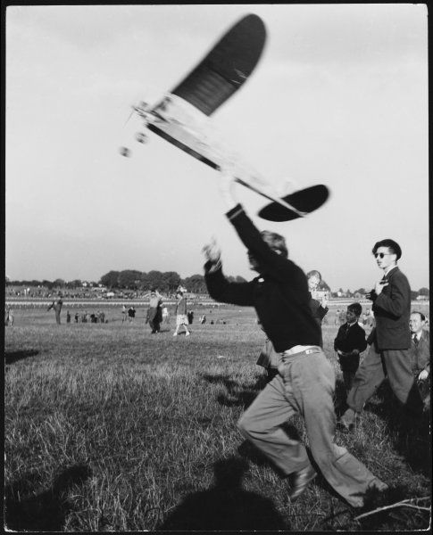 A young man runs along and attempts to get his model aeroplane to fly, at a model aeroplane show