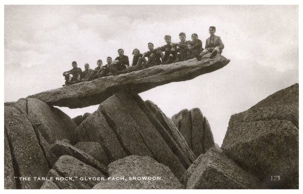 Schoolboys sitting on The Table Rock, Glyder Fach, Snowdon, North Wales Date: circa 1930s