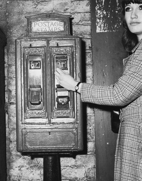 Stamp Machine 1960S. A young woman puts a penny