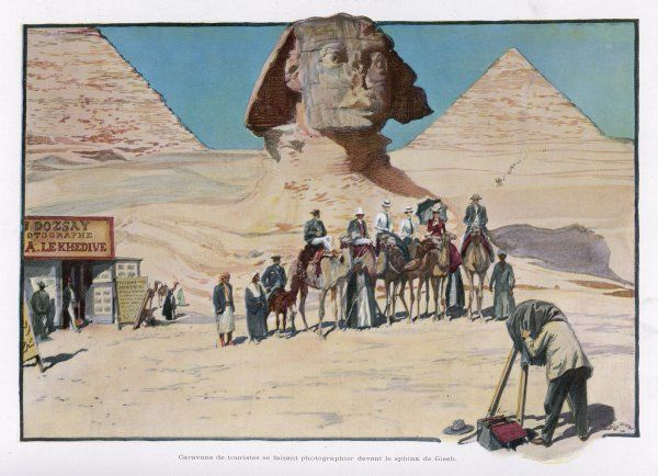 Tourists are photographed in front of the Sphinx - some are on camels