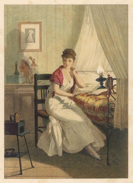A woman sits on a chair beside her bed reading a book by lamplight