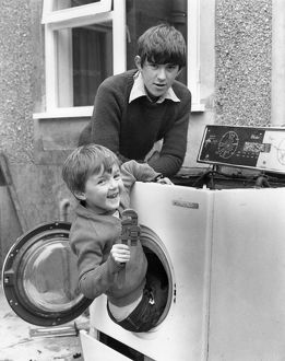 Two boys playing in old washing machine