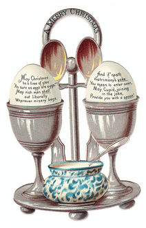 Eggcup stand with two eggs on a cutout Christmas card