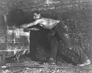 Welsh miner in coal mine pushing truck